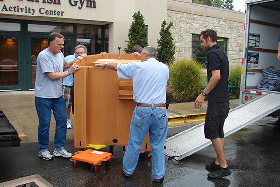 Nativity director of ministries Tom Garbach (left) and Knights of Columbus members load the heavy ambo onto a truck bound for Joplin, Mo. The ambo, along with other altar furniture, was donated to St. Mary Parish in Joplin, which was destroyed in a tornado.