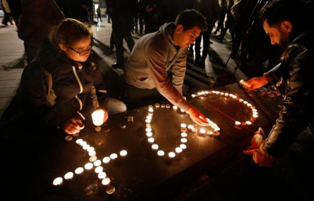 People light candles in the shape of a cross and heart in Republique square in Paris Nov. 14 in memory of victims of terrorist attacks. Coordinated attacks the previous evening claimed the lives of 129 people. The Islamic State claimed responsibility. (CNS photo/Paul Haring)
