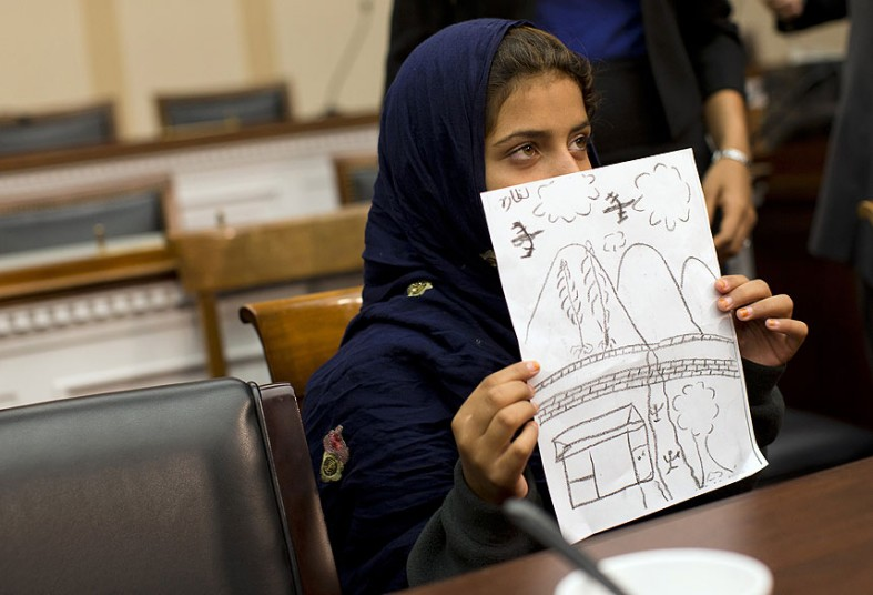 """Children used to draw birds in the sky, not drones Nine-year-old Nabila Rehman holds a photo with a drawing she made depicting a drone strike that killed her grandmother, during a news conference on Capitol Hill in Washington."" Rep. Alan Grayson, D-Fla. invited Pakistani teacher Rafiq ur Rehman and his children, Nabila, and 13-year-old son Zubair, to speak about a drone strike that killed Rafiq's mother, Mammana Bibi, in the remote tribal region of North Waziristan. Picture: Evan Vucci/AP Photo"