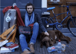 a young man, assumed to be a student sitting on the sidewalk against a wall. Surrounded by suitcases, university books and other personal items , petting a dog lying on the left of hum, behind the dog a bike