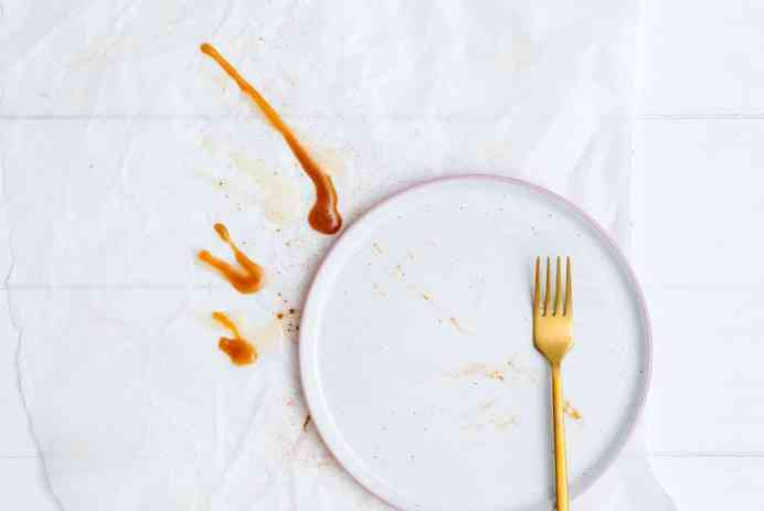 gold fork on top of empty white plate