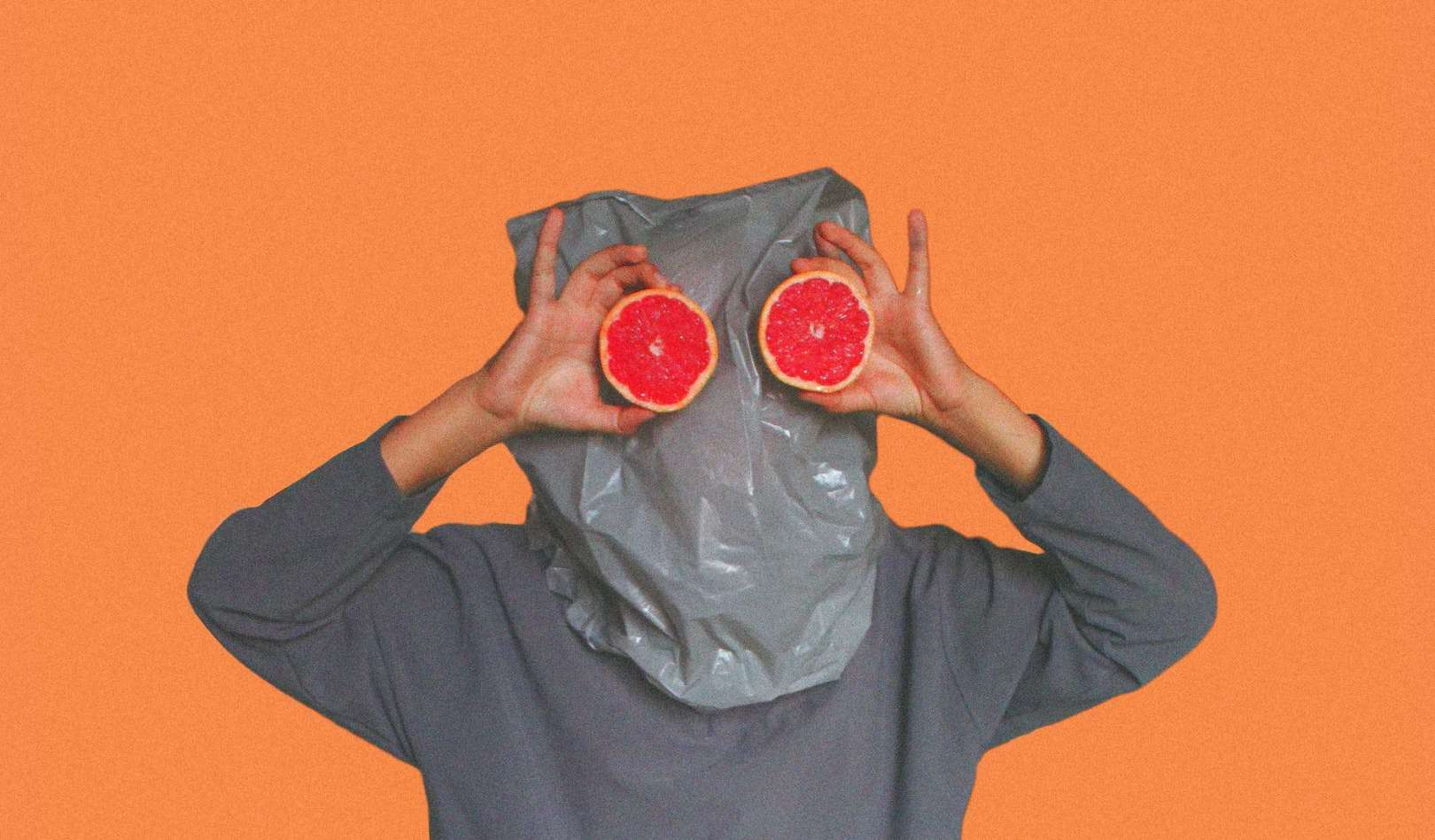 person covered with plastic bag on head while holding sliced blood orange