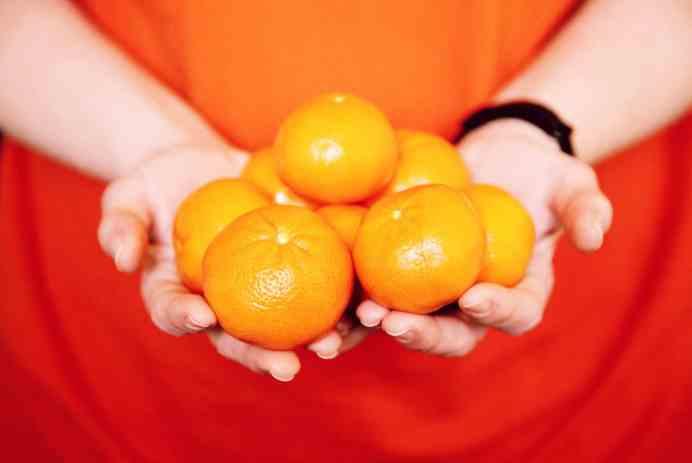 person holding orange fruits in close up photography