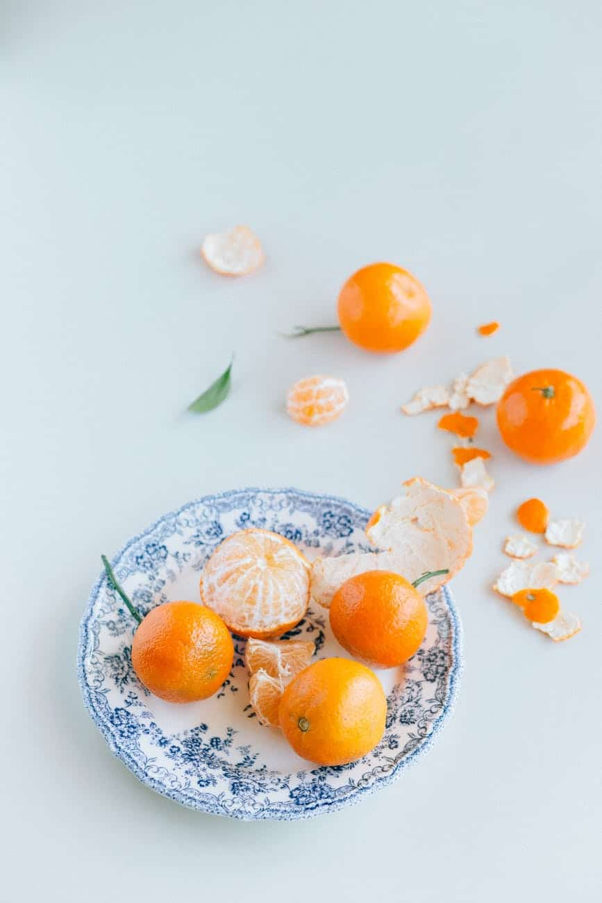 orange fruits on white and blue floral ceramic plate