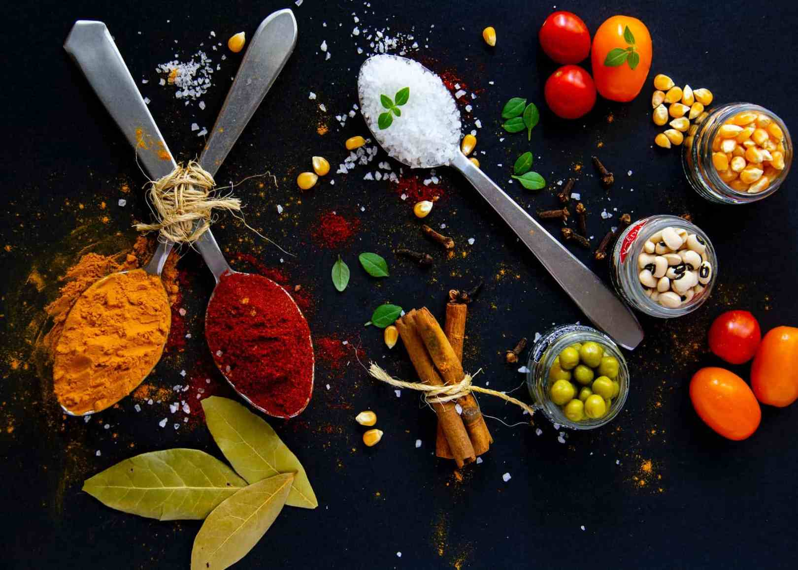 collection of bright spices and fresh vegetables on table