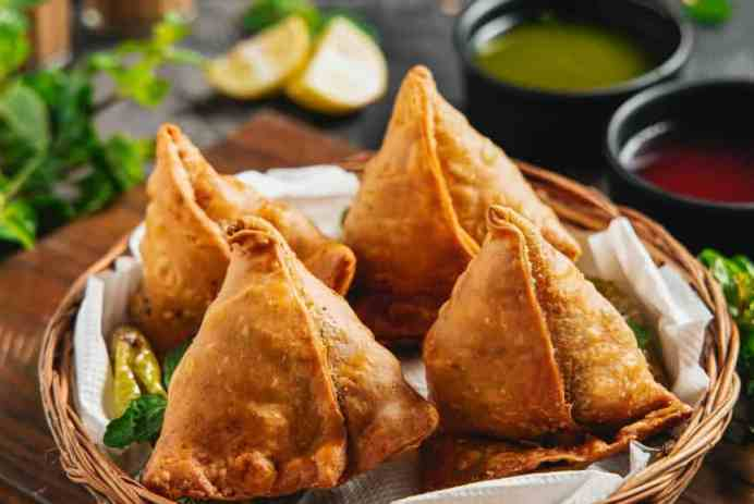 samosas in wicker basket on dinner table
