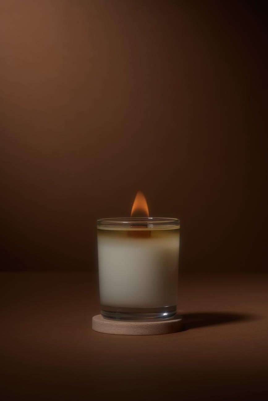 lighting aroma candle on brown table