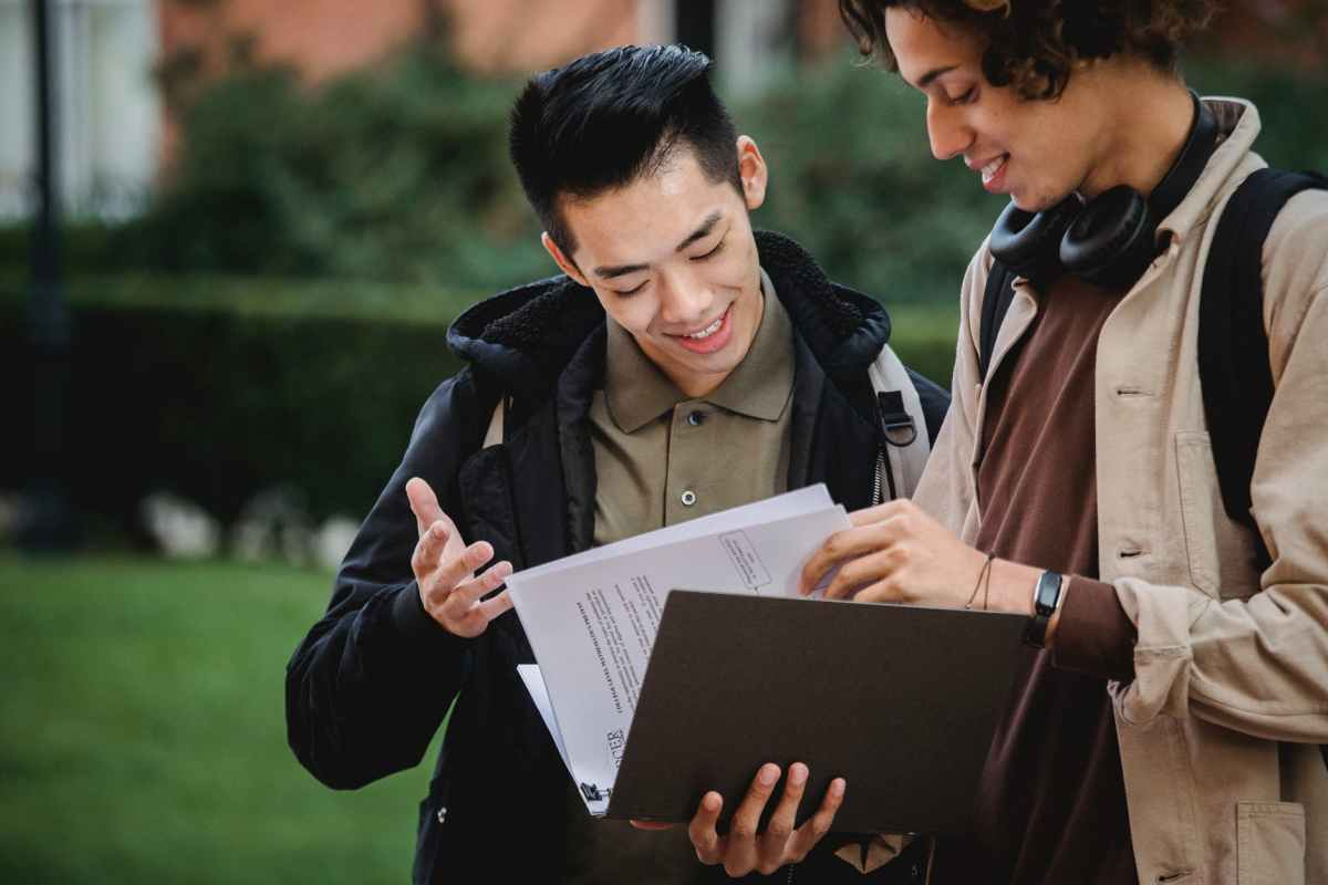multiethnic students reading report in folder together