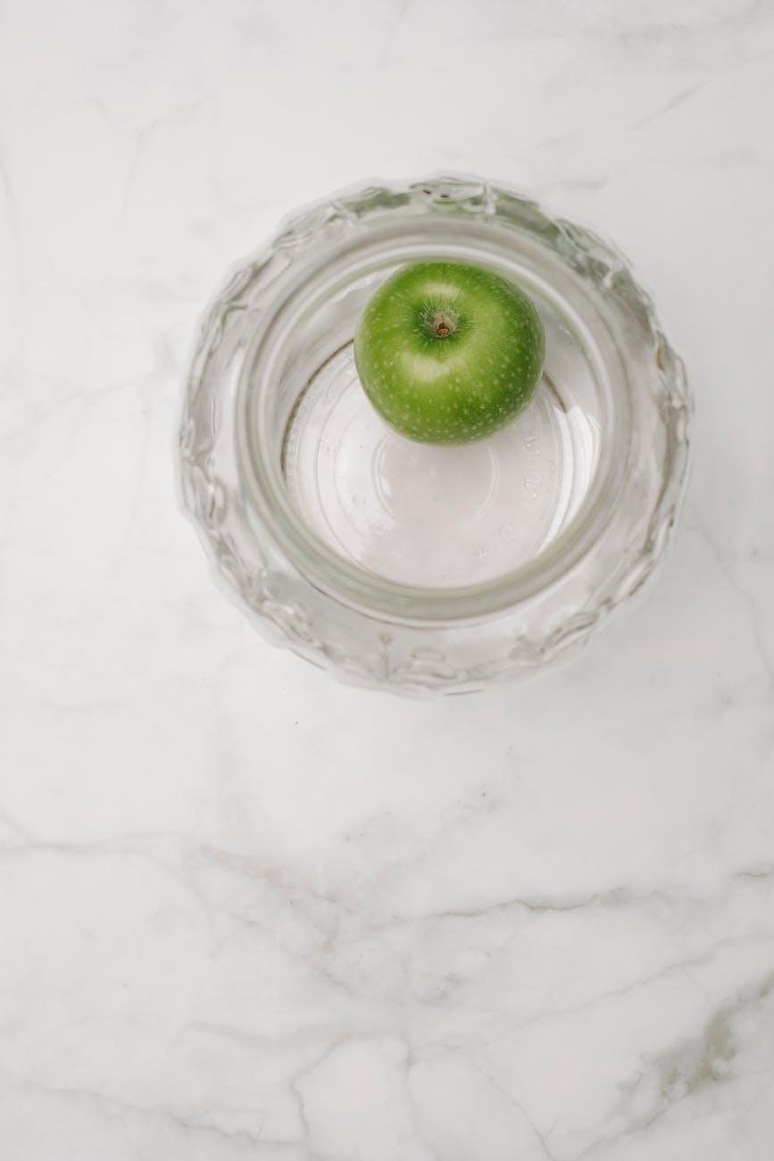single green apple in glass bowl