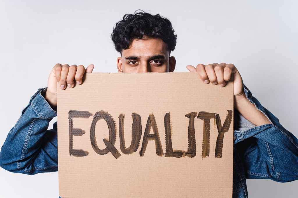 man holding cardboard with equality text