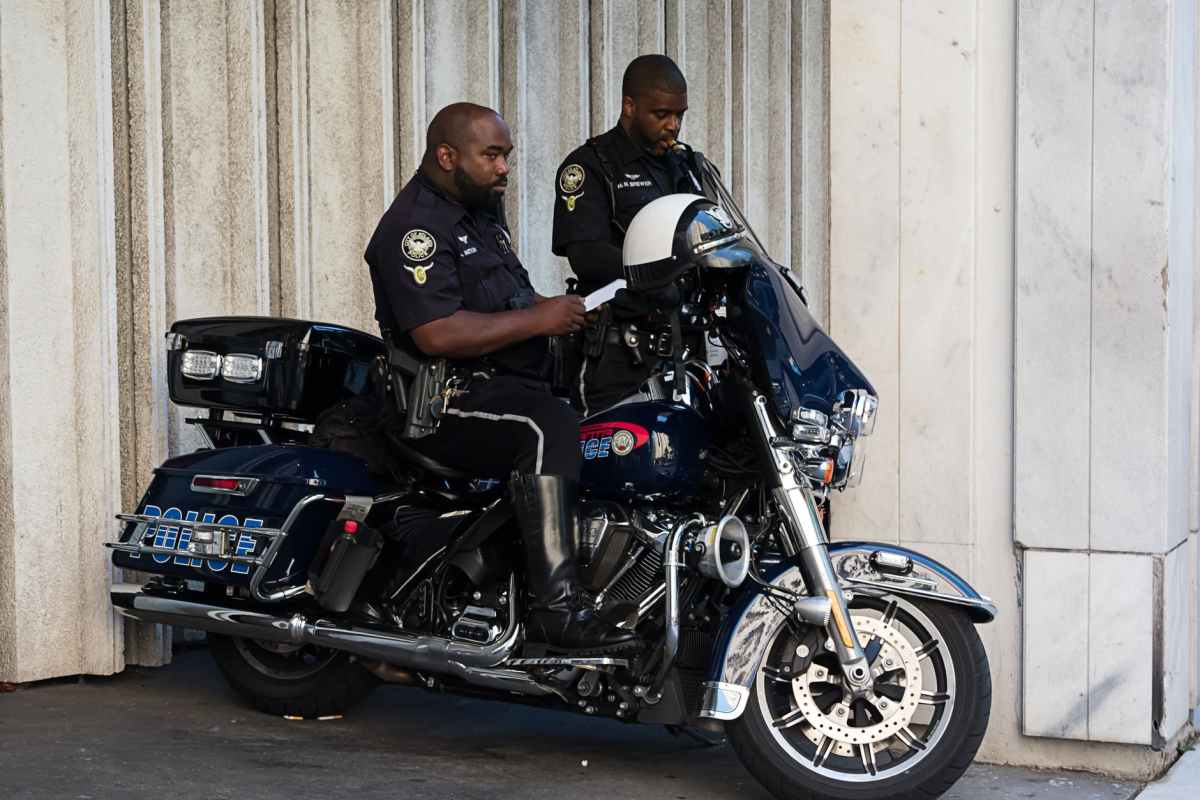 standing police man beside another man who seats of police motorcycle