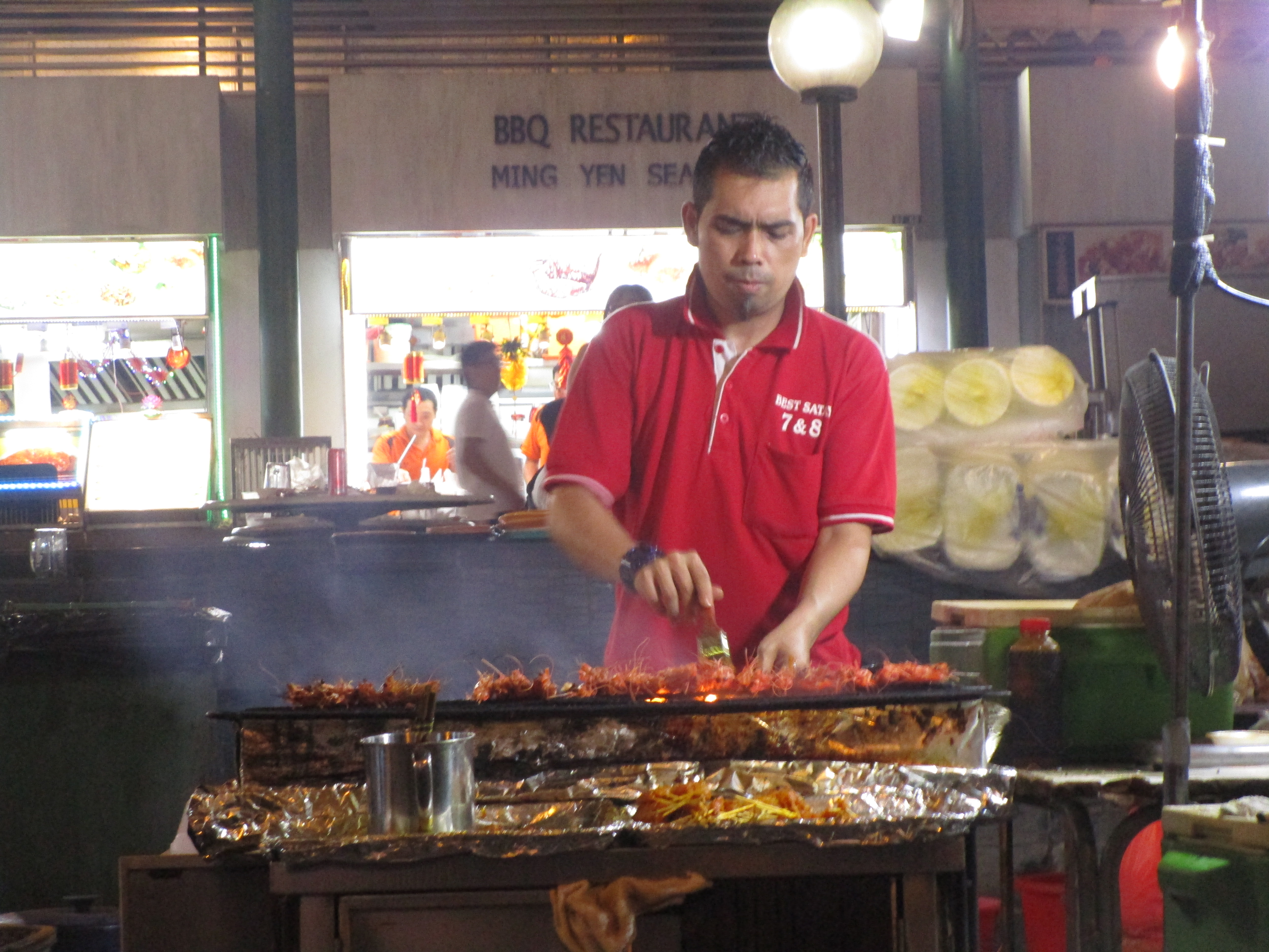 Grilling beef, lamb, and chicken at the Satay Club in Singapore