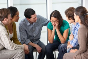 People sit together in a circle with their attention focused on one group member with her hands on the sides of her face as she looks sadly down.