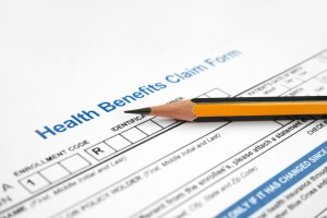 A black and yellow pencils sits atop a form titled Health Benefits Claim Form.