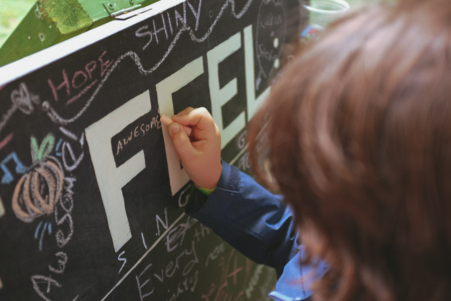 Child writing 'feel awesome' on a chalk board