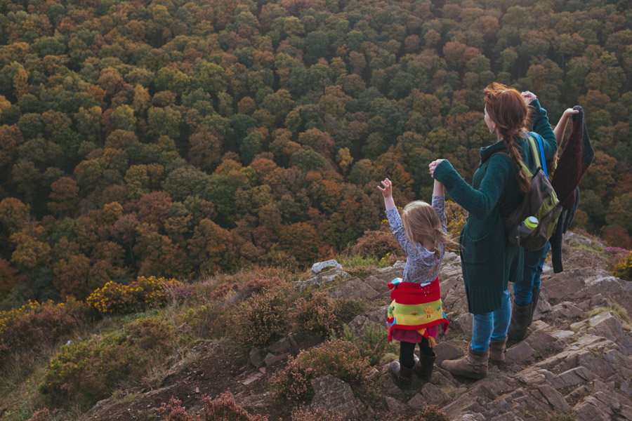 Picture of a family standing on a high precipice with arms stretched out in celebration