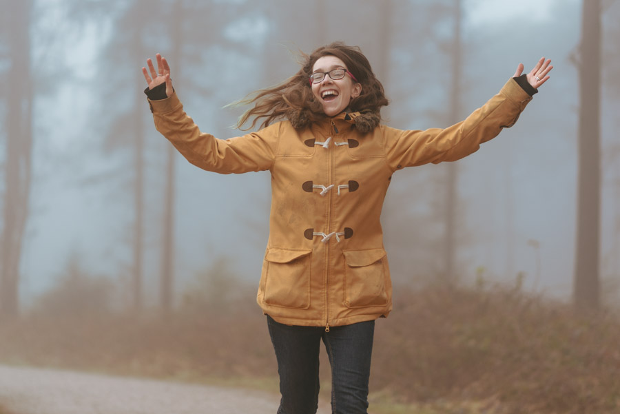 image of a woman in a yellow coat, running through the woods grinning, arms outstretched
