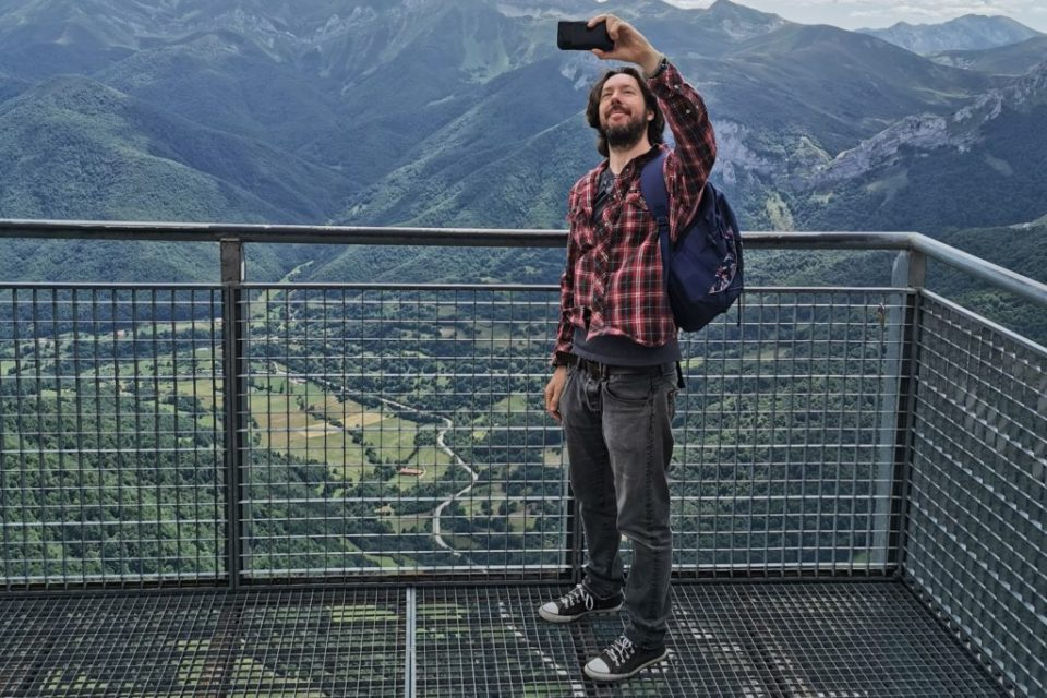 image of a man taking a selfie from a viewing platform at the top of a mountain