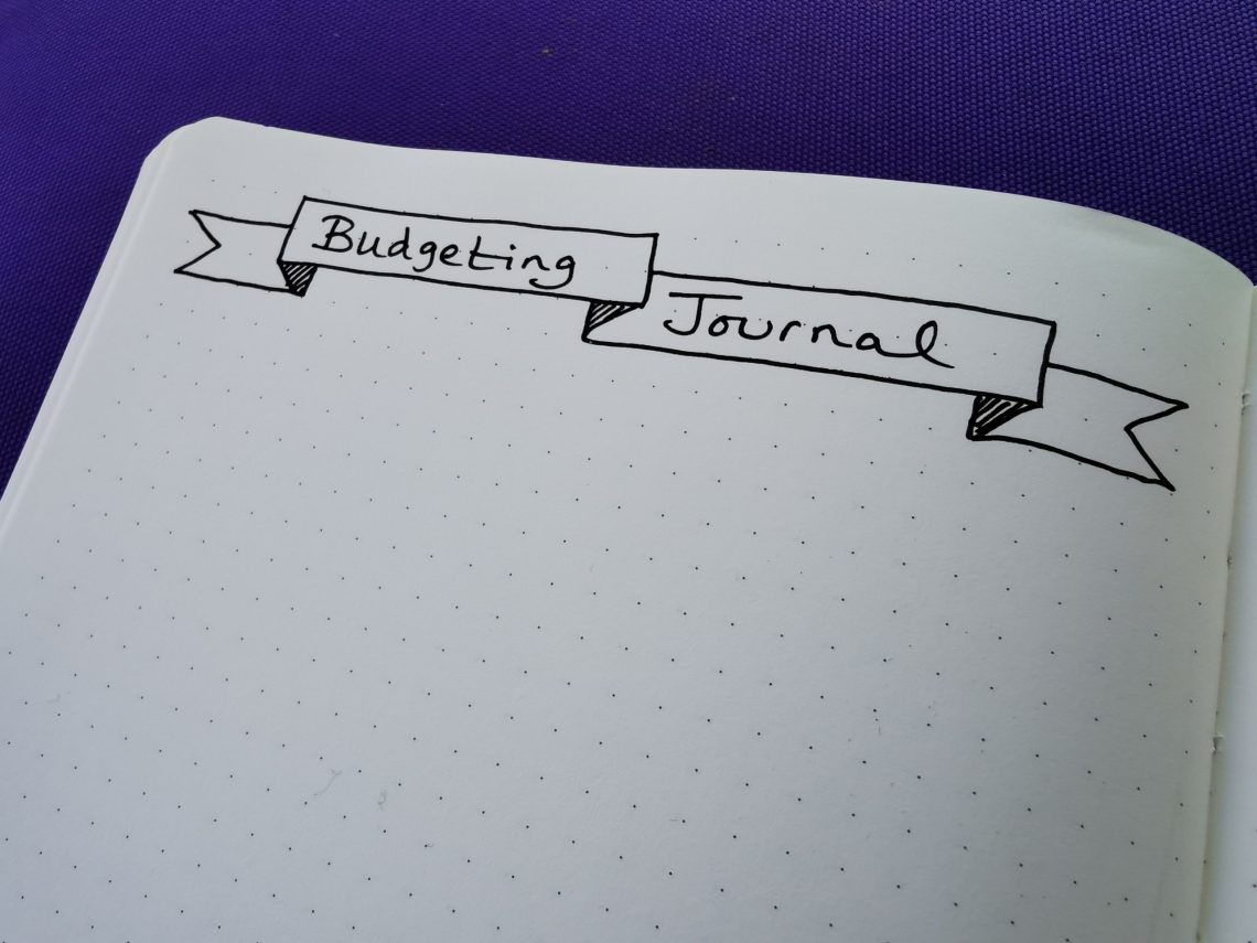 "An image of a hand-drawn banner in a bullet journal with the title ""budgeting journal"""