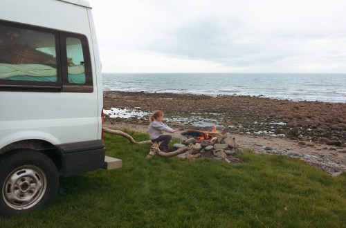 IMage of a young girl sat by a campfire behind a campervan