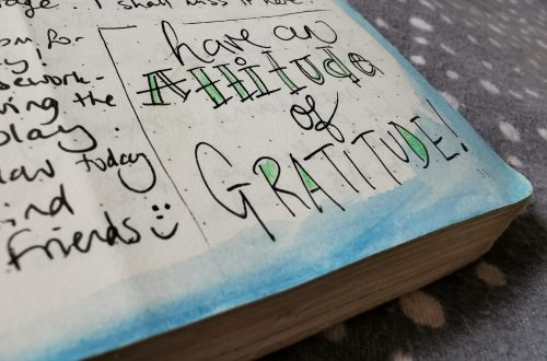 Image of text in a notebook saying 'have an attitude of gratitude'