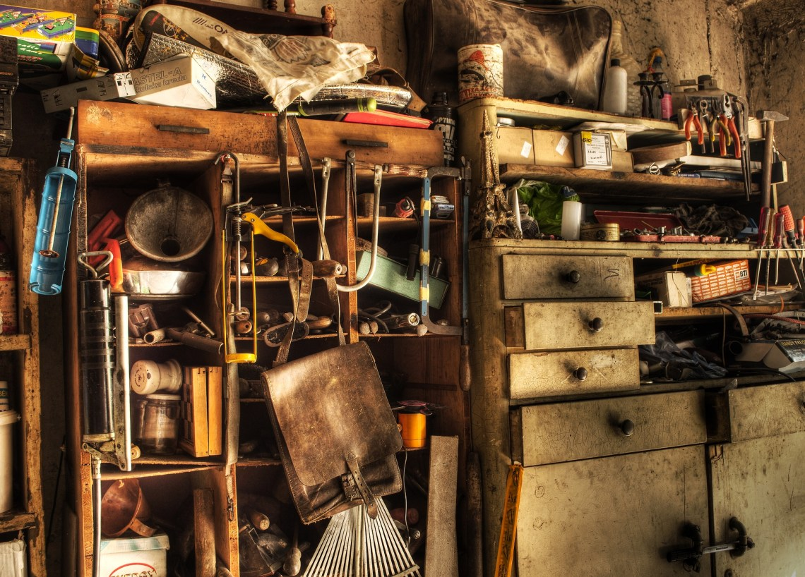 Image of a cluttered garage/workspace filled with tools and overflowing drawers