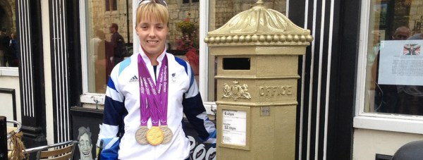 Local Paralympian Sophie Wells with her gold postbox in uphill Lincoln.