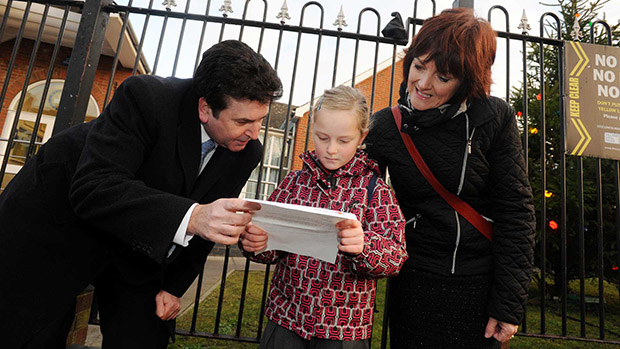 Chief Executive of City of Lincoln Council Andrew Taylor reads Sophie's letter with mum Karen outside her school. Photo: Stuart Wilde