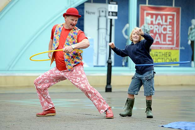 Leo the Clown teaches 9-year-old Rowan Ley to hoola-hoop.