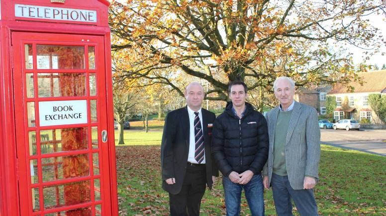 West Lindsey District Councillor Roger Patterson, Parish Councillor Gavin Monks and Ingham Parish Council chairman Keith Wagstaff by the village green's renovated phone box book exchange.