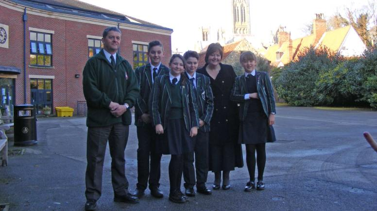 Lincoln Minster School will be the first to benefit from a new defibrillator unit from LIVES. Pictured: students with Paul Martin (LIVES) and Mandy Taylor (LMS Business Manager)