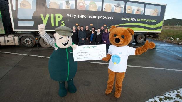 Company mascot Billy Branston holding a £10,000 cheque for St Barnabas Hospice