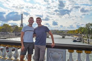 Scott Swiontek and John Line on a bridge over the Seine River with the Eiffel Tower in the background, Paris, France.