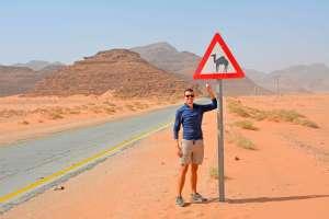 John Line pointing to a camel road sign, Petra, Jordan.