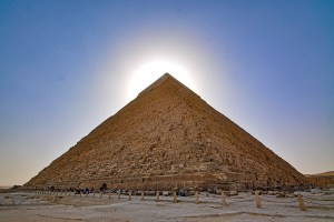 The sun behind one of the Pyramids of Giza, Cairo, Egypt.