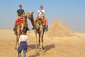 Scott Swiontek and John Line riding camels in front of the Pyramids of Giza, Cairo, Egypt.