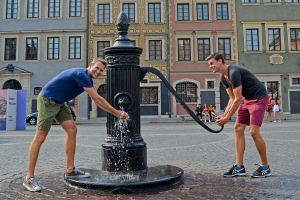 Scott Swiontek and John Line at a water well in Old Town, Warsaw, Poland.