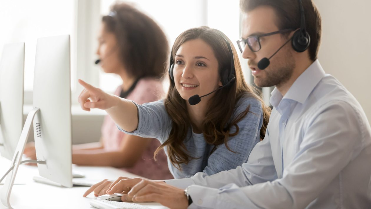 Female call center agent helping male colleague pointing at computer