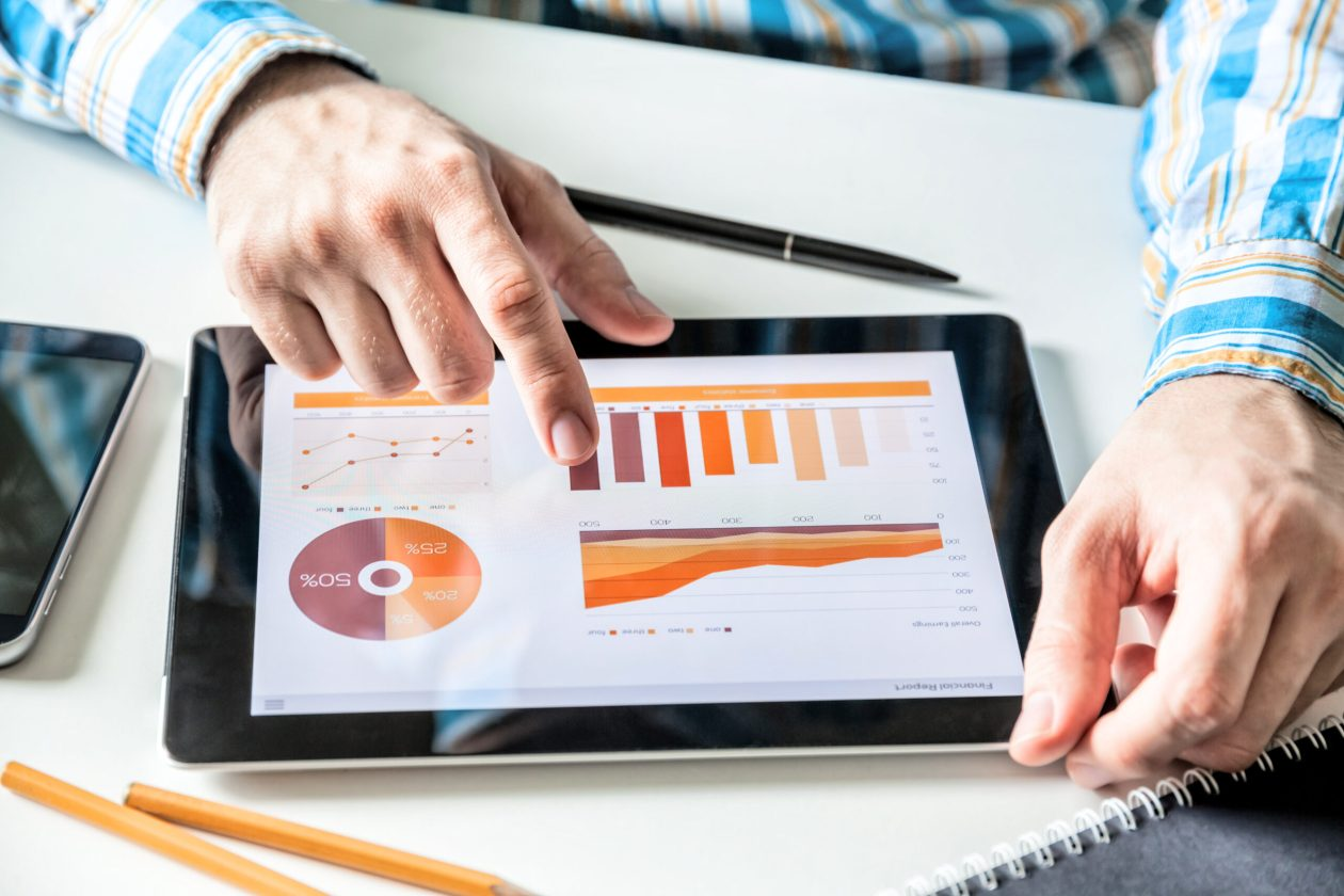 Businessman working with digital Tablet computer with finance report in Office. Business market Research, Economic statistics concept