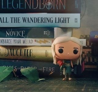 Game of Thrones pop standing in front of a stack of books