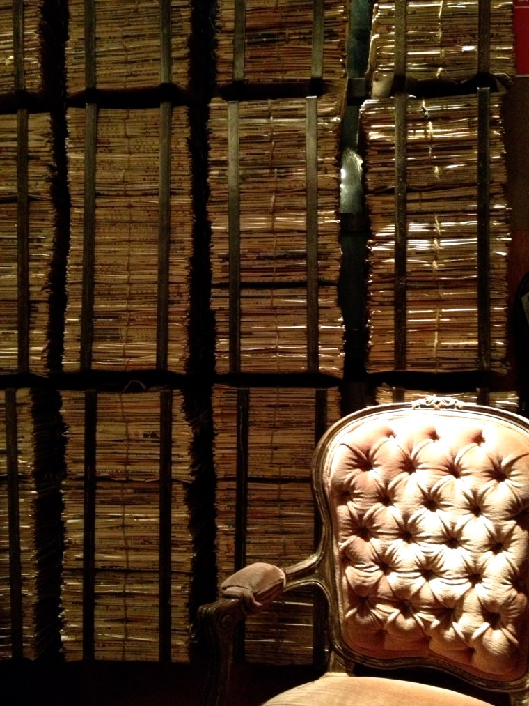 wall of paper and vintage chair