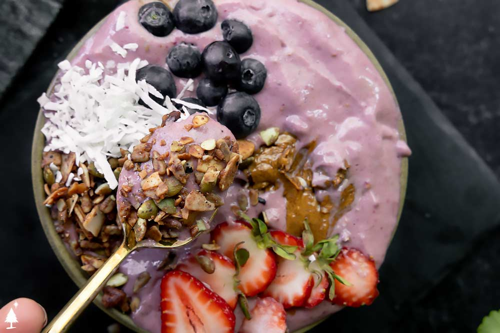 scooped Keto Berry smoothie bowl with berry toppings
