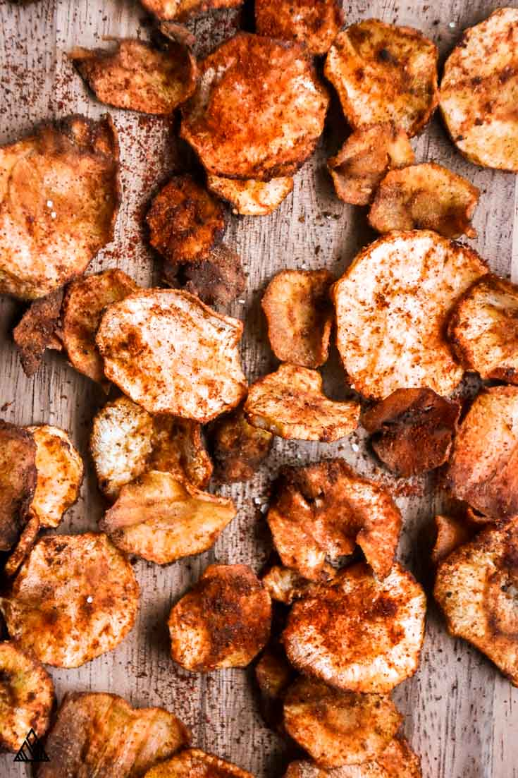 parsnip chips on cutting board with red and orange spices
