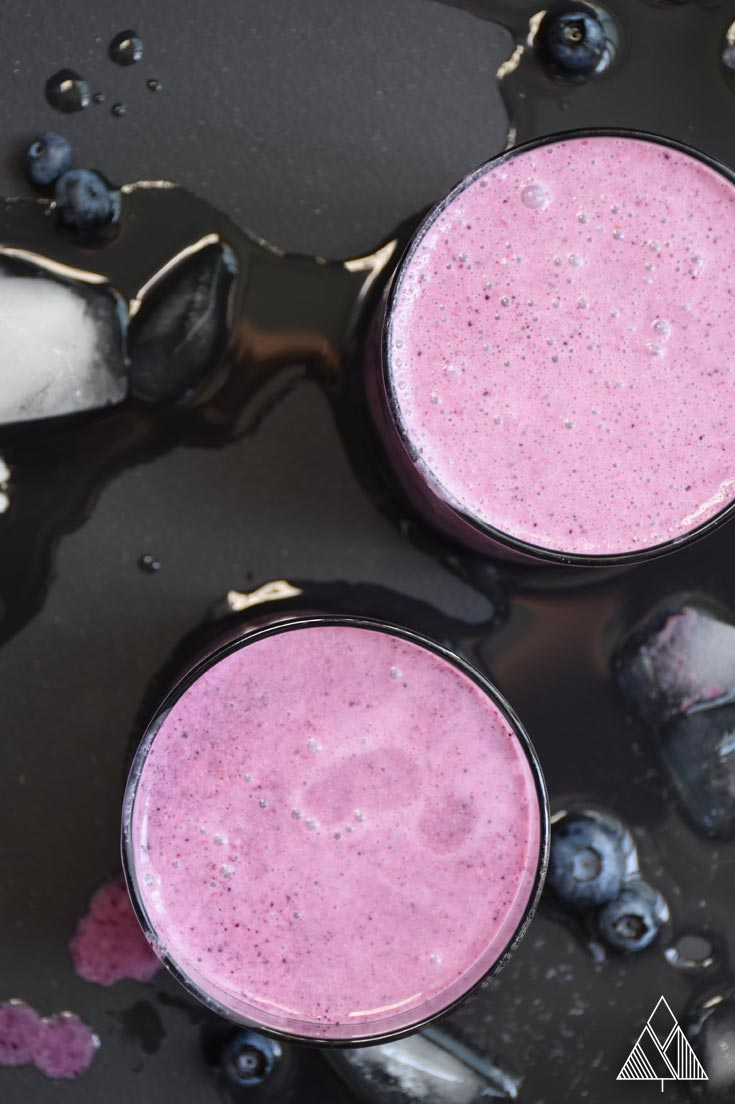 2 glasses of a healthy blueberry smoothie on a black background with melted ice and blueberries