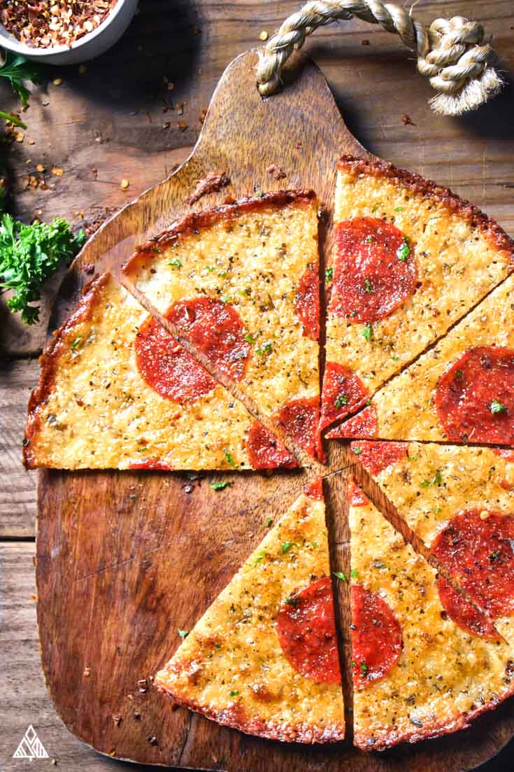 Crustless pizza on a cutting board, cut into slices, with parsley in the corner
