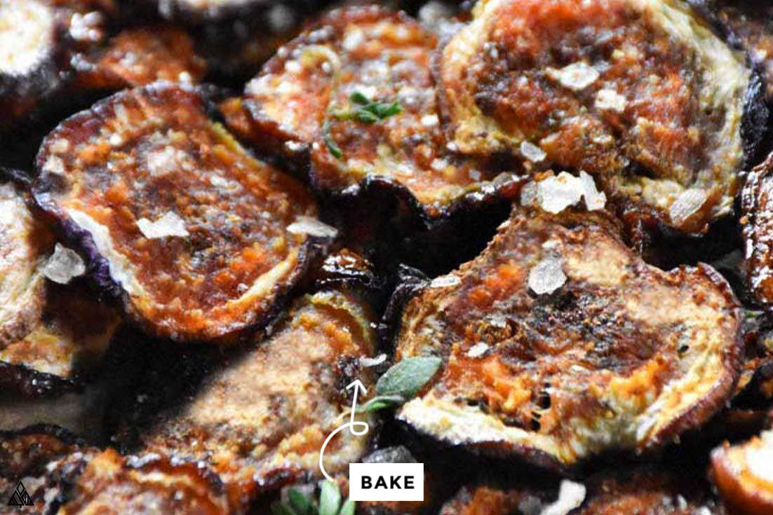 easy baked eggplant chips on a baking sheet with salt