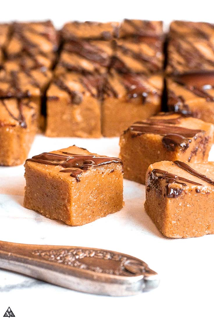 Low carb peanut butter fudge, sliced with knife and a few pieces in front