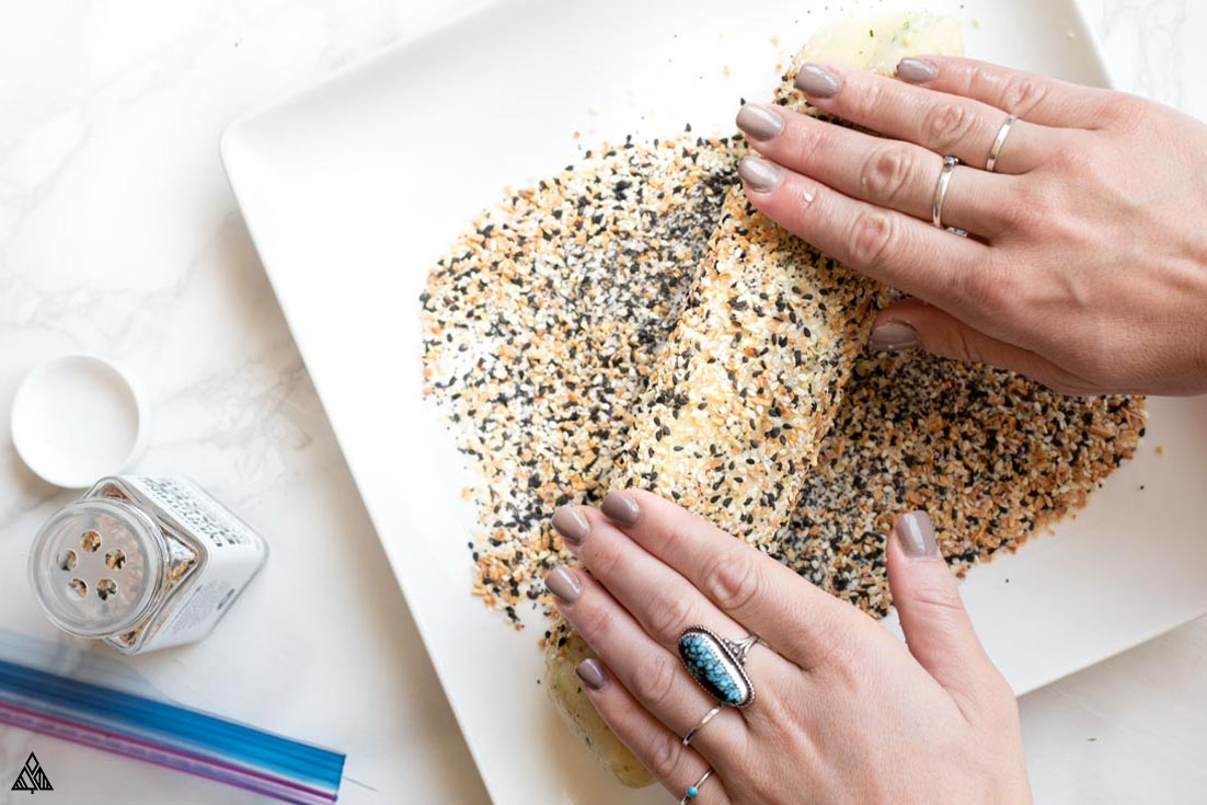 Rolling the dough into a plate full of sesame seeds