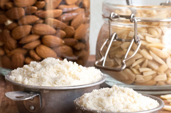 Almond nuts in a jar and almond flour in a measuring cup
