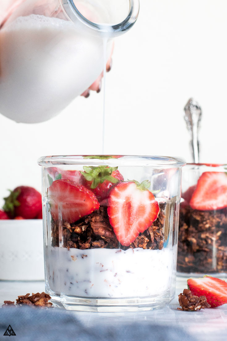Pouring milk into a glass of low carb chocolate granola